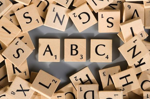 Scrabble pieces with numerous different letters forming ABC